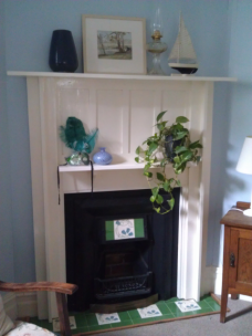 The fireplace holds a collection of little things including an antique painting