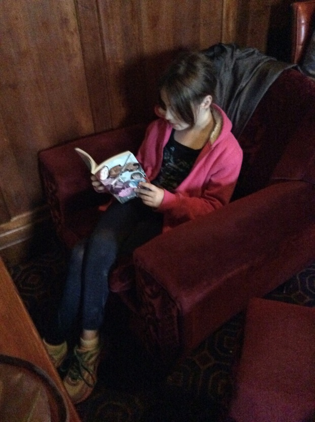 India reading her book on the cool and grungy club lounge